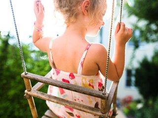 Fille sur une balançoire au jardin